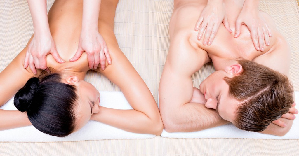 Portrait of beautiful couple lying  in a spa salon enjoying a deep tissue back massage together.